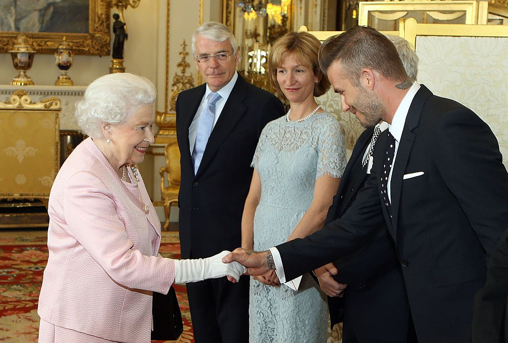Britain's Queen Elizabeth II (L) shakes hands with former England footballer David Beckham (R) as former prime minister John Major (2L) looks on during a reception