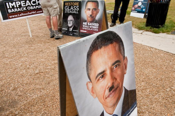 A picture of President Barack Obama with a Hitler-like mustache is seen at a stand of controversial politician Lyndon LaRouche's movement during a march of supporters.