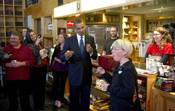 President Barack Obama (C) eats a doughnut with U.S. Sen. Patty Murray (2nd L) as he stops at Top Pot Doughnuts in Seattle.