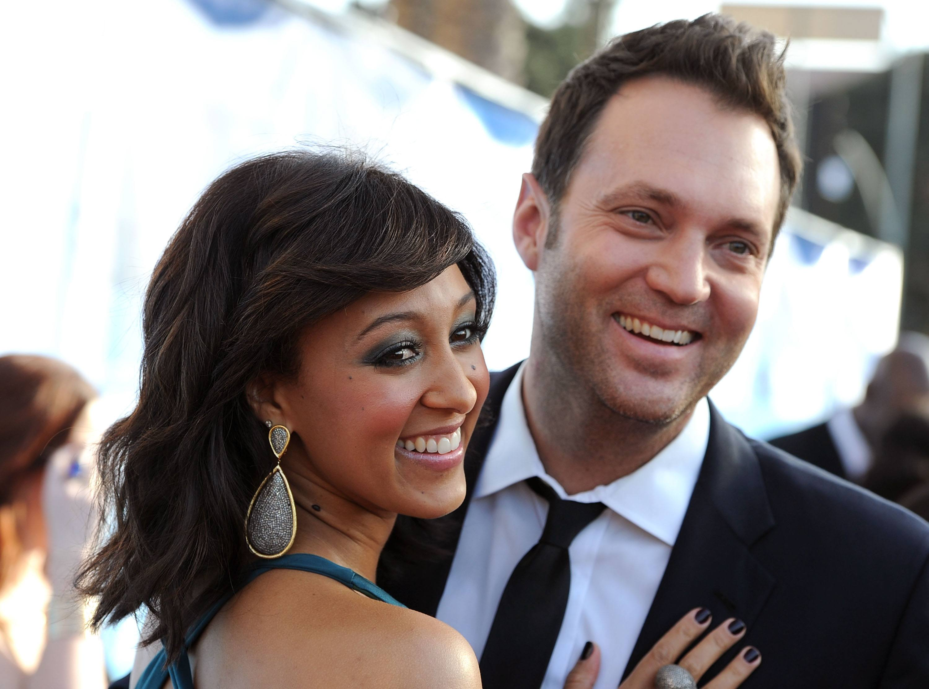 Actress Tamera Mowry and reporter Adam Housley arrive at the 42nd NAACP Image Awards held at The Shrine Auditorium on March 4, 2011 in Los Angeles, California.