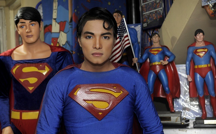 """Filopino fashion designer Herbert Chavez dresses like the """"Man of Steel"""" as he stands among his huge collection of Superman mannequins, dolls and other paraphernalia at his home in Calamba, south of Manila, on October 13, 2011."""