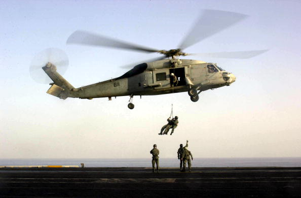 "US Navy SEALs train with an SH-60F ""Seahawk"" helicopter on the flight d"