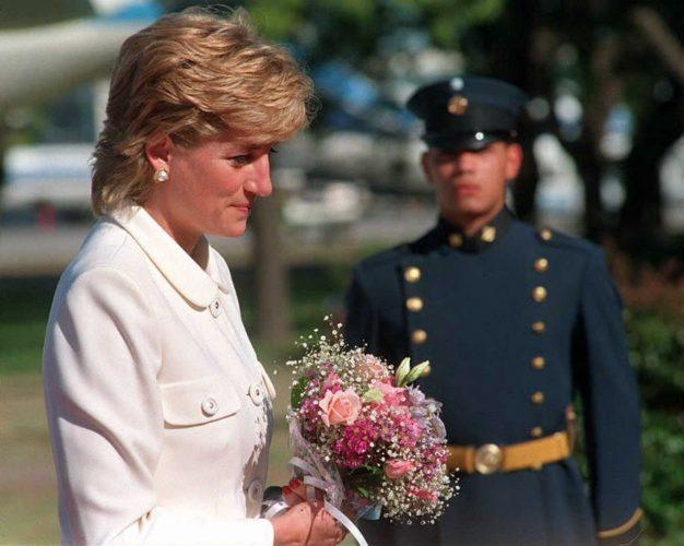 Princess Diana holding flowers during a ceremony.