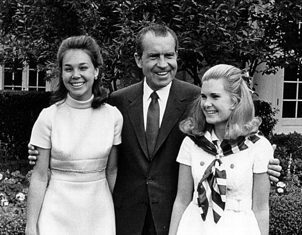 President Richard Nixon laughs with his daughters, Julie (left) and Tricia.