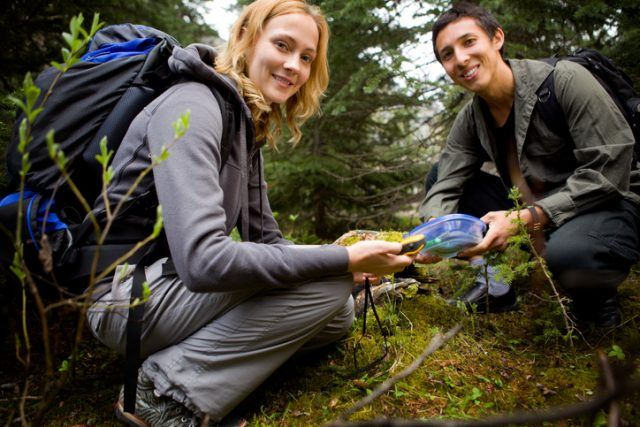 Two people finding a geocache in the forest