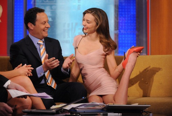 Brian Kilmeade looks on as Miranda Kerr demonstrates a yoga pose
