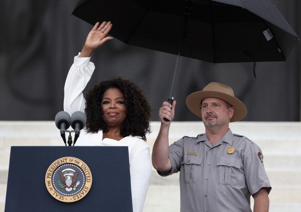 oprah at the lincoln memorial with a ranger holding an umbrella over her head