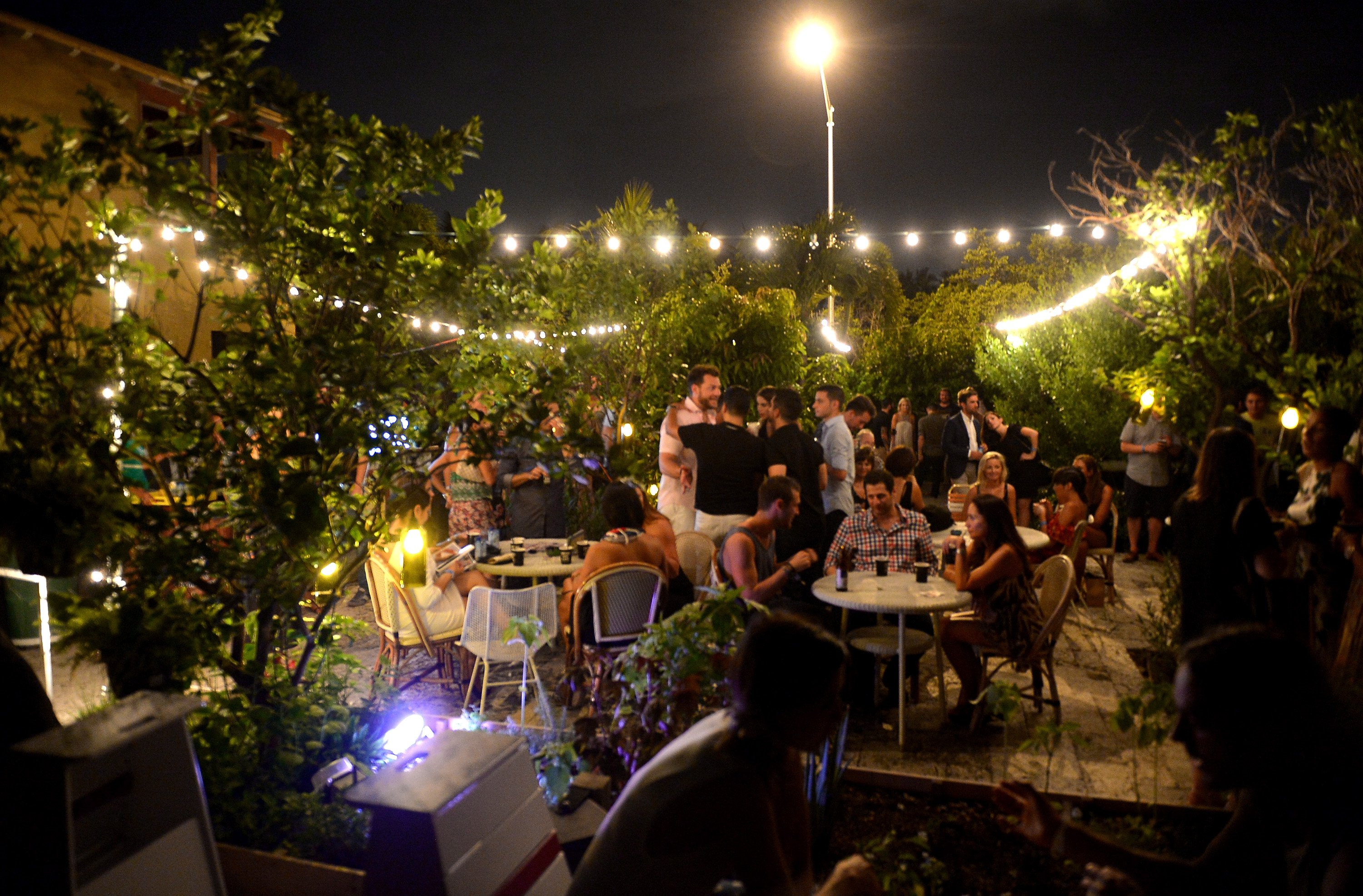 people at a rooftop party with string lights
