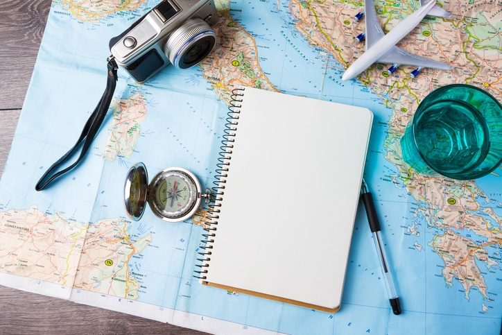 a camera and notebook spread over a map