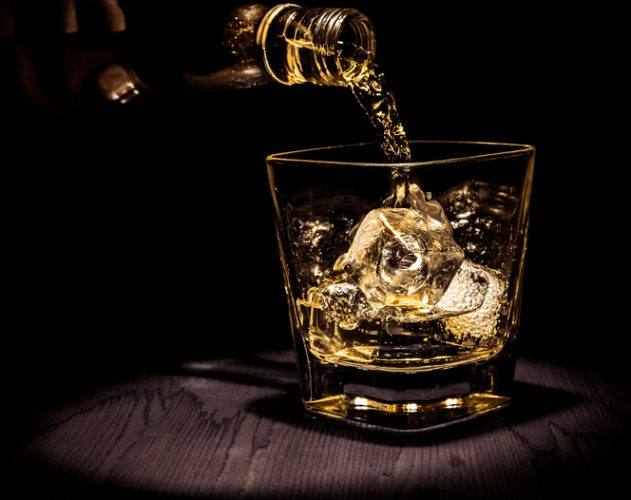 barman pouring whiskey in the glass on wood table, warm atmosphere, old style, time of relax with whisky with space for text