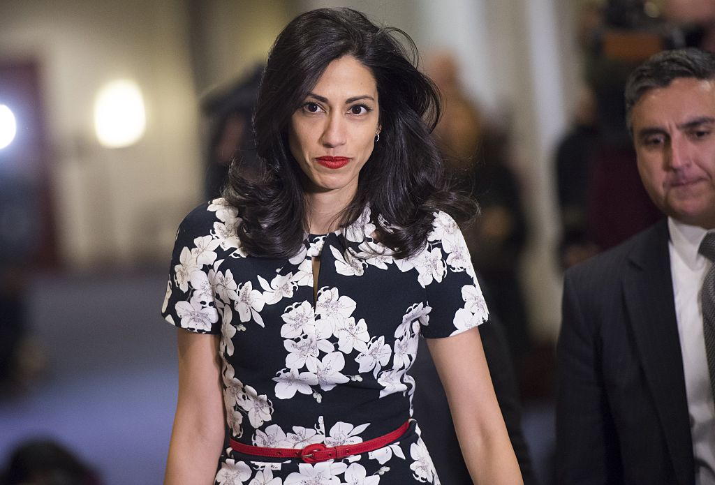 huma abedin walking in a black and white floral dress and red belt