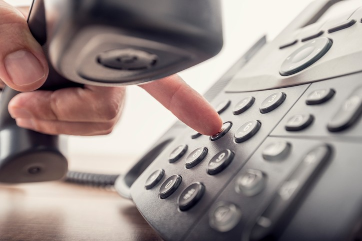 Closeup of male hand holding telephone receiver while dialing a telephone number to make a call using a black landline phone. With retro filter effect