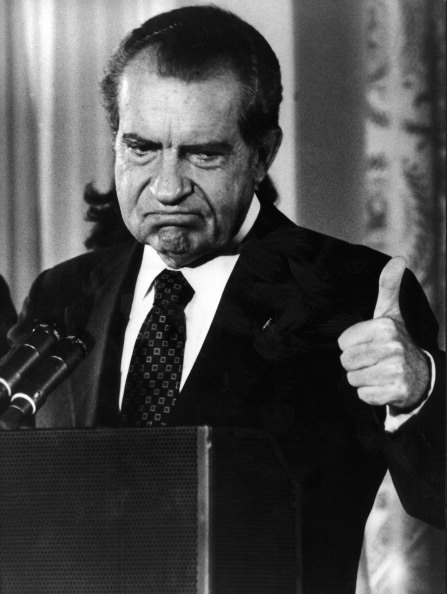 Nixon gives a thumbs-up after announcing his resignation