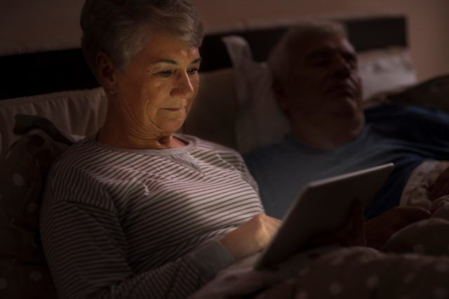 Grandmother browsing the Internet late at the night