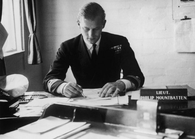 Prince Phillip writing at a desk.