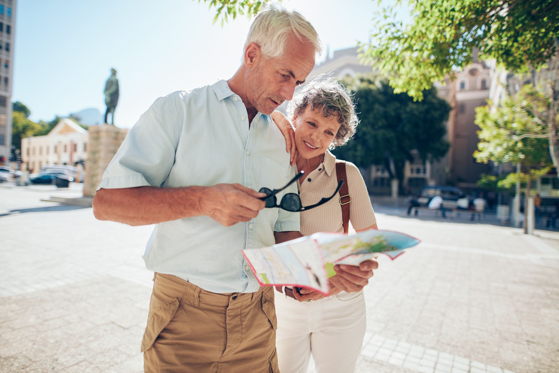 senior couple reading a map while traveling