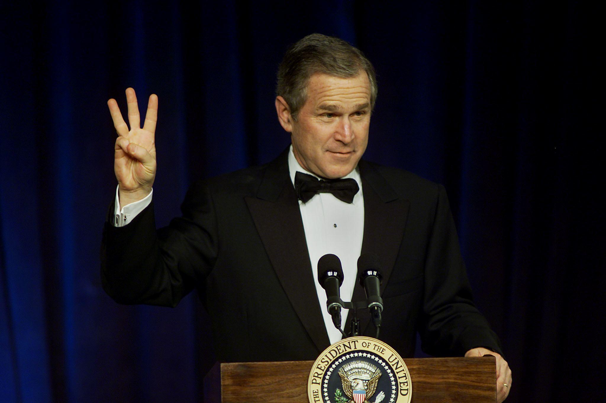 """George W. Bush flashes a """"W"""" sign."""