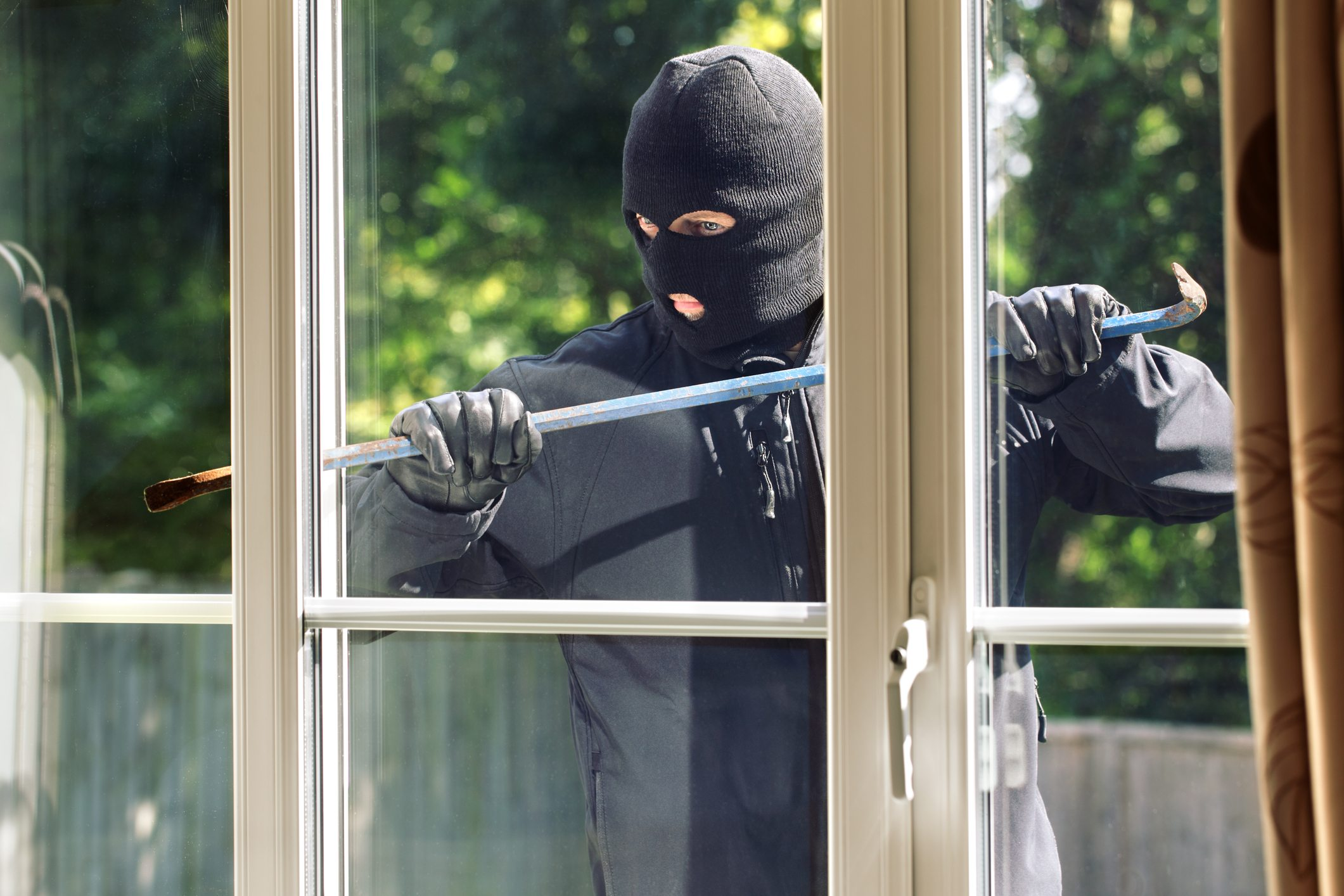 Burglar breaking into a house via a window with a crowbar