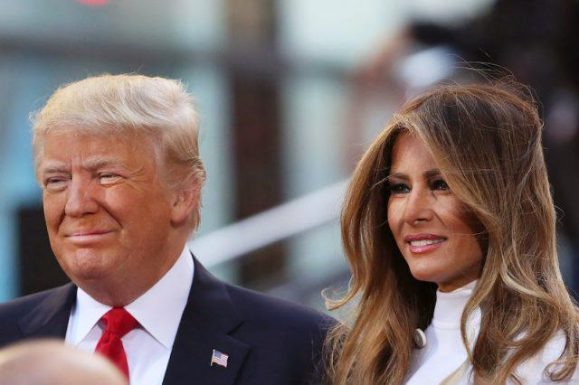 Republican presidential candidate Donald Trump sits with his wife Melania Trump.