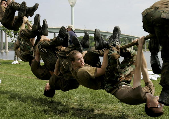 navy cadets hanging upside down on a rope