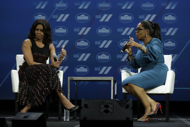 US First lady Michelle Obama (L) gestures next to Oprah Winfrey on a stage at the White House Summit on the United State of Women in Washington, DC on June 14, 2016.