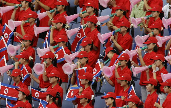 North Korean cheering squad hold their national flag and cheer on track and field athletes in the Asian Athletics Championships