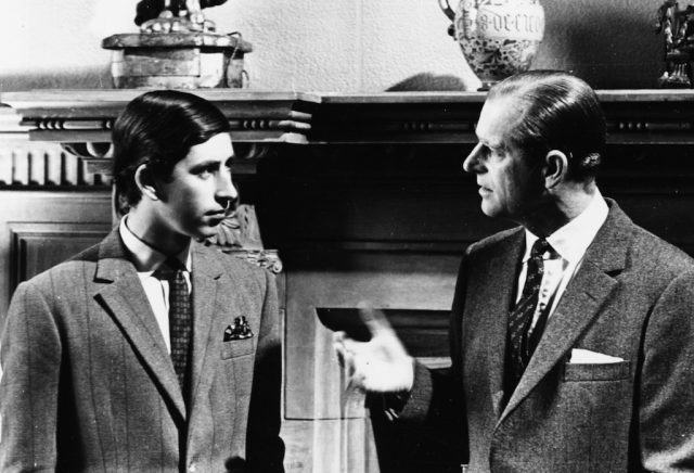 Prince Charles And Prince Phillip speaking together in front of a fireplace.