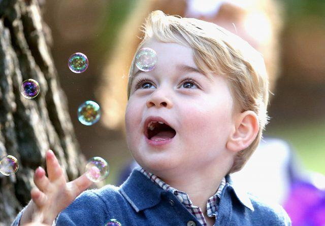 Prince George looks happily at bubbles in the air.