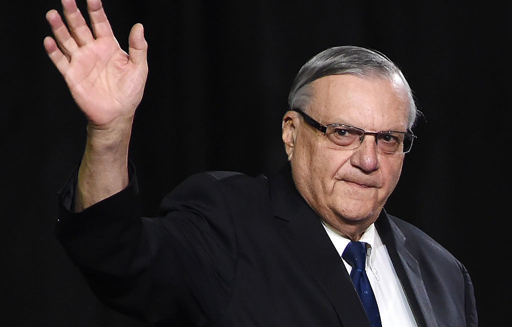 Joe Arpaio in a black suit waving at a crowd