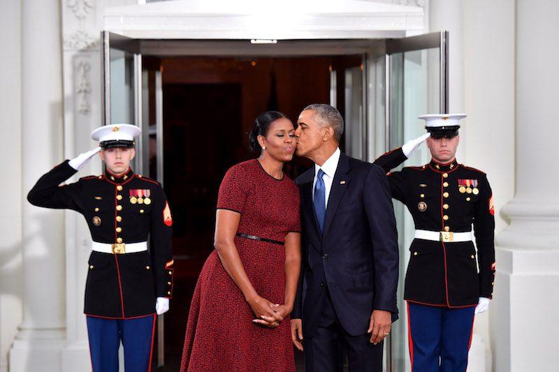 President Barack Obama (R) gives Michelle Obama a kiss