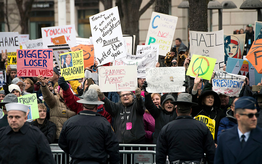 Protesters demonstrate as Trump and first lady Melania Trump walk in the inaugural parade after being sworn January 20, 2017
