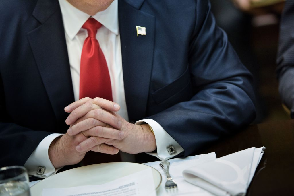 trump's hands folded in front of a dinner plate