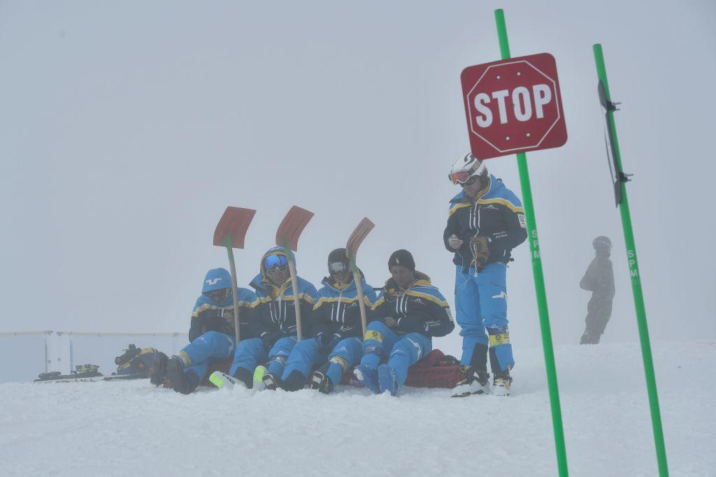 Officials sit on ski slope with shovels