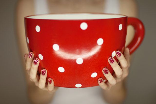 woman hands with red and white fingernails holding a big, giant coffee cup in red with white dots.
