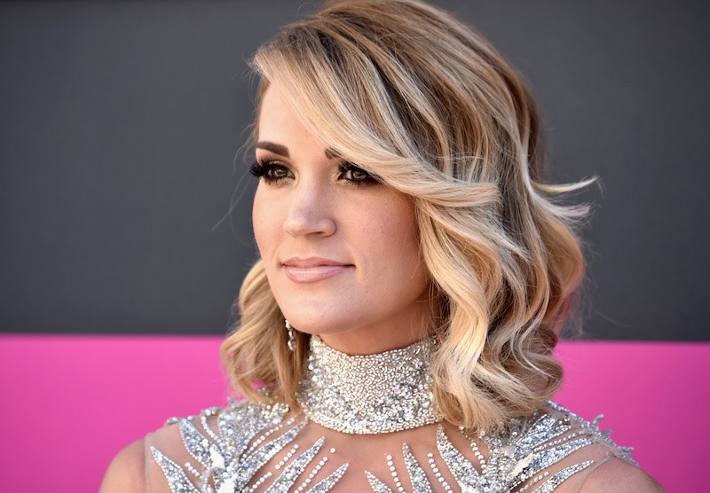 Carrie Underwood smiles while posing on the red carpet