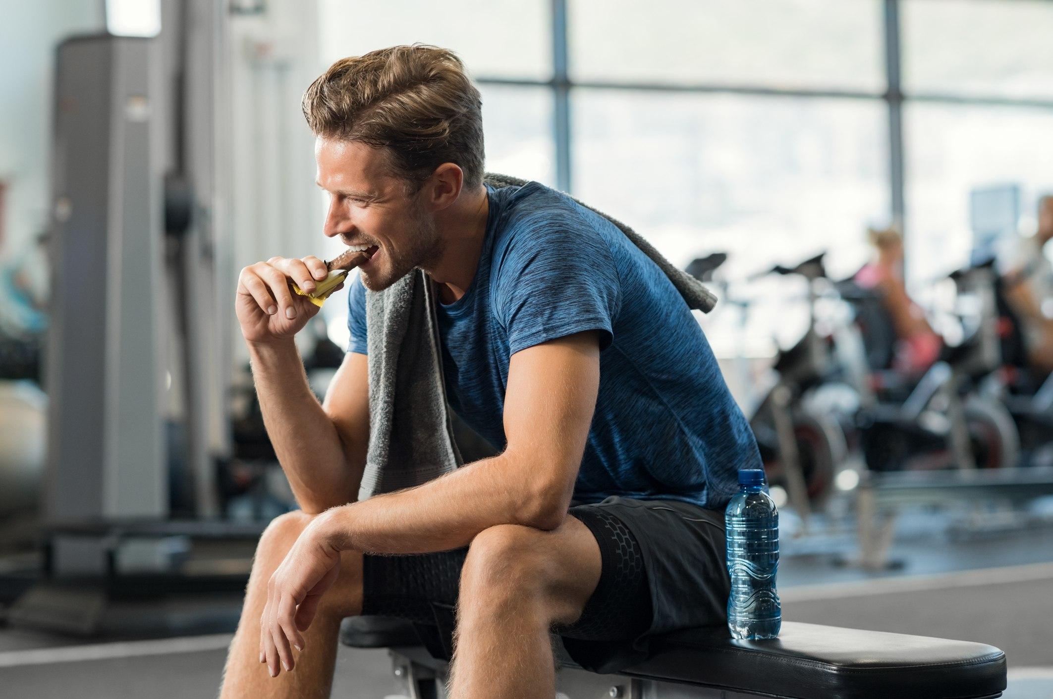 Sweaty young man eating energy bar at gym