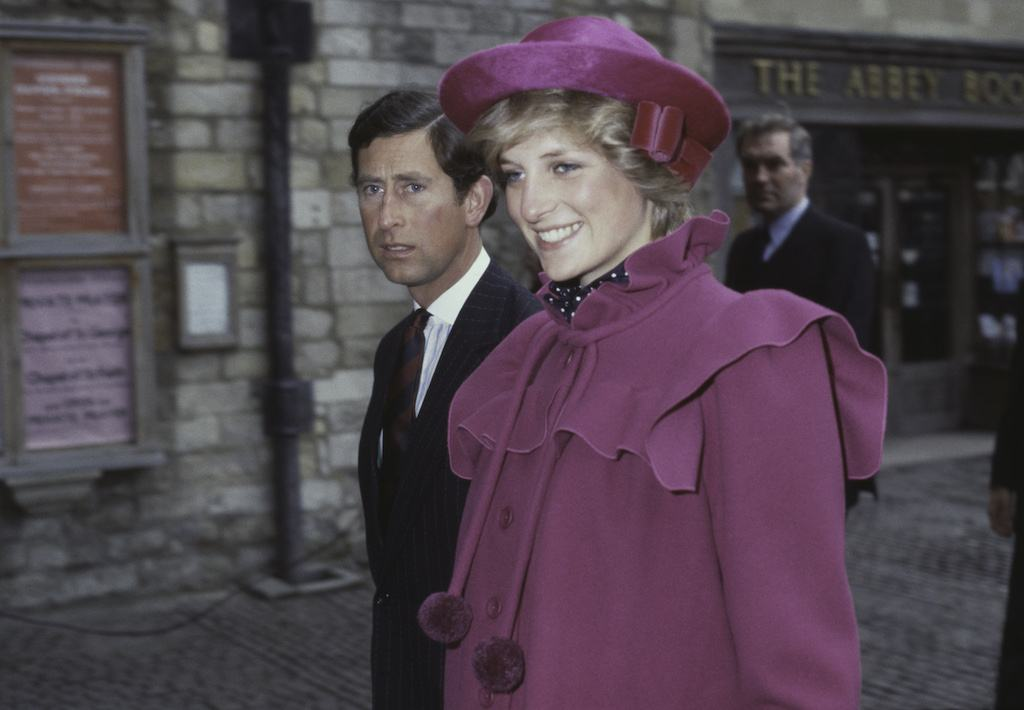 Princess Diana smiling as she walks near Prince Charles.