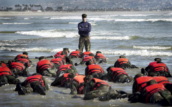 During a Hell Week surf drill evolution, a Navy SEAL instructor assists students from Basic Underwater Demolition class 245 with learning the importance of listening.  