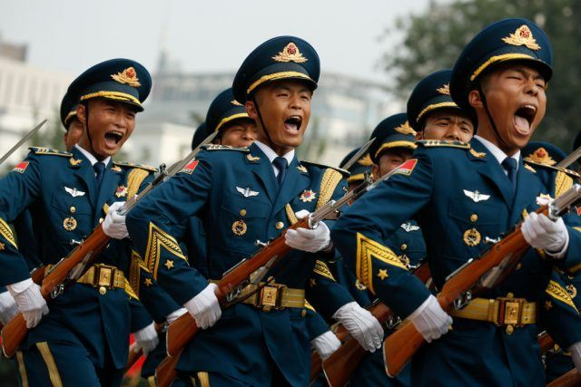 Marching honour guards shout during a welcoming ceremony in Beijing.