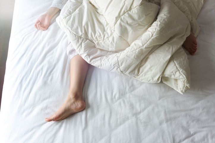Bare Feet of a Young Woman on White Bed