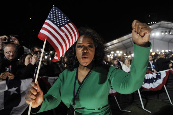 oprah in a green suit with an american flag
