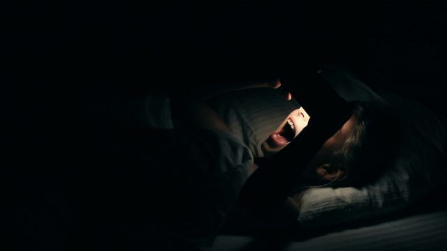Young girl watching video on smartphone lying down in bed. Night shot in bedroom with white girl using cell phone for watching movie or video channel from internet