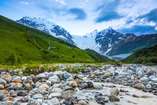 From the river shore, covered with stones, opens view on fantastic glacier and steep rocky mountains with green meadows, which are covered with snow.Happy lifestyle. Beautiful universe.