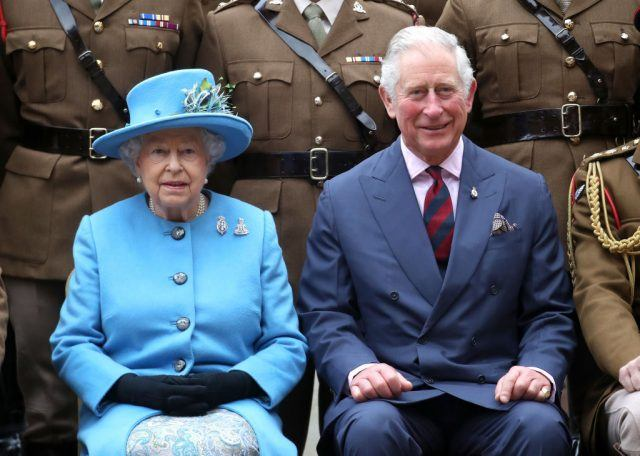 Queen Elizabeth II and Prince Charles sitting together during a ceremony.