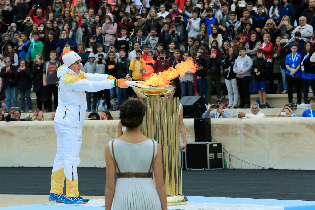 Ioannis Proios lights the Olympic torch during a handover ceremony for the Olympic Flame at Panathenaic stadium in Athens, on Tuesday, Oct. 31, 2017.