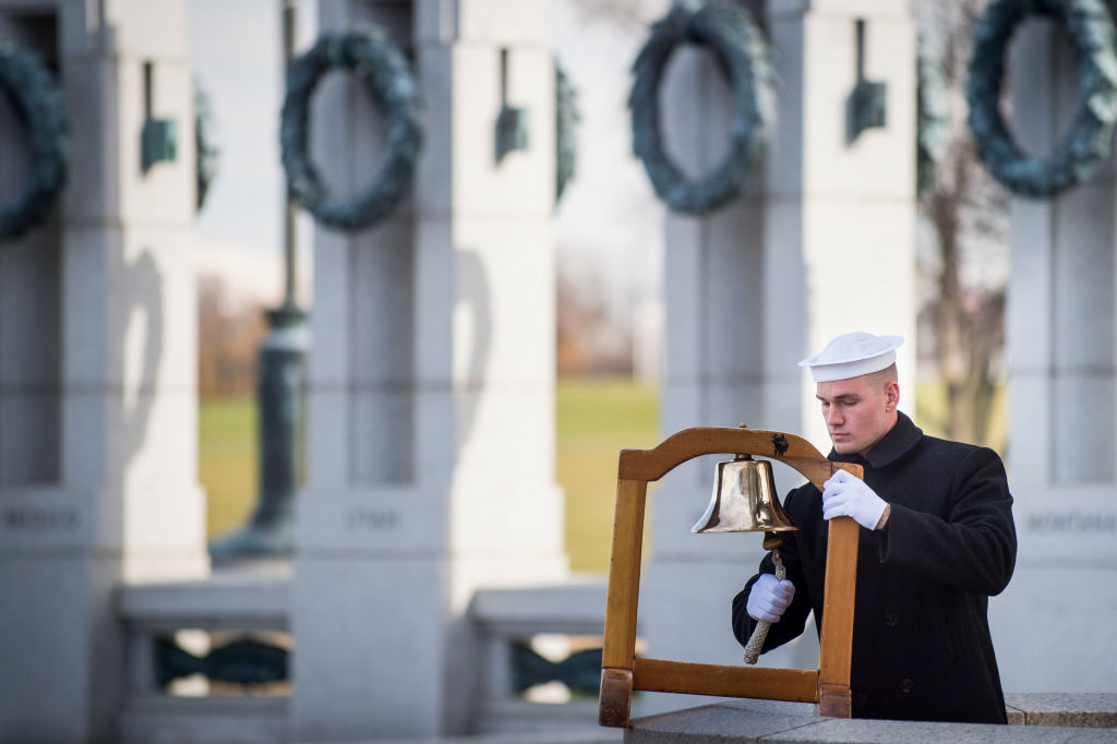 A serviceman with the US Navy, ring a ships bell to mark the time of the Japanese attack on Pearl Harbor during the Friends of the National World War II Memorial and the National Park Service, commemorate Pearl Harbor Remembrance Day