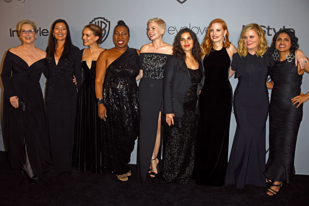 Many women dressed in black smiling and posing together