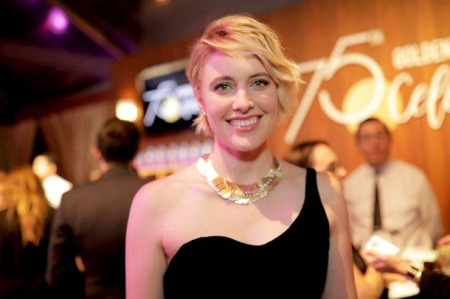 Greta Gerwig smiles while posing in a black dress and gold necklace.