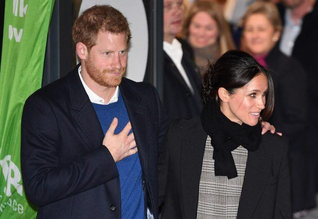 Prince Harry and Meghan Markle standing together in front of a crowd.