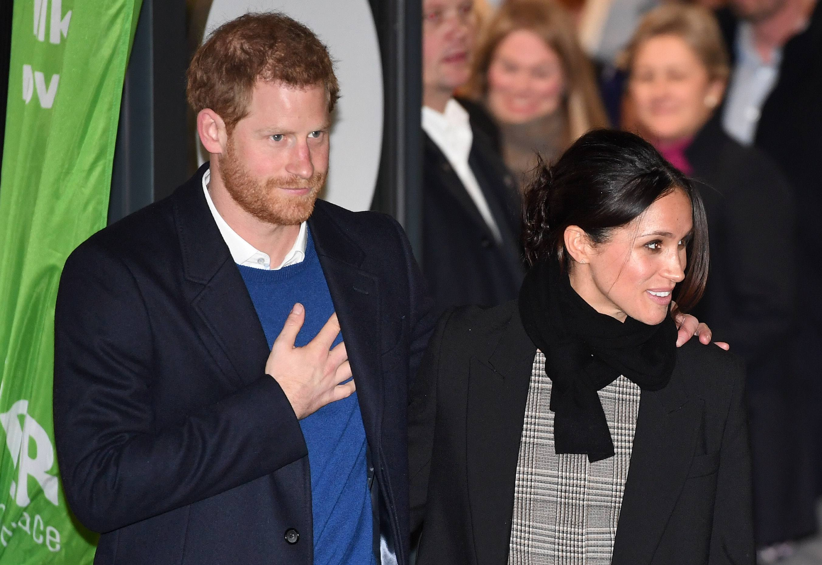 Prince Harry (L) and fiancee Meghan Markle leave after their visit to Star Hub